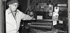 älterer Mann mit Mütze vor Synthesizer mit Knöpfen und Schalttafeln