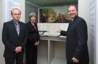 Farbphotographie: Frau und zwei Männer stehen vor einer Vitrine, in der eine Notenhandschrift und ein Gemälde zu sehen sind