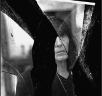 Schwarz-Weiß-Photographie: Portrait einer dunkelhaarigen Frau, die sich in Spiegelscherben spiegelt
