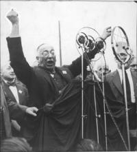 Schwarz-Weiß-Portraitphotographie: Mann hält eine leidenschaftliche Rede vor einem Mikrophon, reißt die Arme hoch