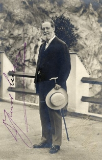 Schwarz-weiß-Photographie: Mann mit Vollbart, Gehstock und Hut in der linken Hand