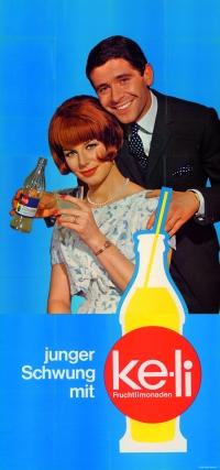 Plakat: lächelnde rothaarige Frau sitzt mit einem Glas in der Hand, hinter ihr steht ein lächelnder Mann im Anzug mit einer Flasche in der Hand