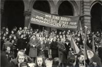 Schwarz-Weiß-Photographie: Menschenmenge mit Transparent vorm Wiener Rathaus
