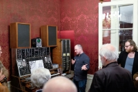 Mann steht vor einem Synthesizer und erklärt den umstehenden Personen die Funktionsweise