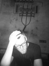 Schwarz-Weiß-Photographie: junger Mann mit Brille und Bart stützt Kopf auf Hand