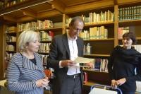 zwei Frauen und ein Mann betrachten in einer Bibliothek ein handschriftliches Dokument.