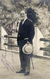 Schwarz-weiß-Photographie: Mann mit Vollbart, Gehstock und Hut in der linken Hand, auf einer Brücke stehend