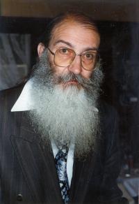 Farb-Portraitphotographie: Mann mit runder Brille, langem weiß-grauem Bart, Krawatte und gestreiftem Sakko