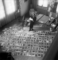 Schwarz-Weiß-Portraitphotographie: stehender Mann mit einem Stück Papier in der Hand, vor ihm am Boden aufgebreitet zahlreiche Bilder