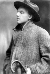 Schwarz-Weiß-Photographie: junger Mann mit Hut, Mantel und Spazierstock