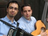 Farbphotographie: zwei Männer sitzend in blauen Hemden, linker Mann mit Knopfharmonika, rechter Mann mit Kontragitarre