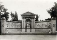 Schwarz-Weiß-Photographie: Denkmal aus Stein, in der Mitte eine sitzende Figur, links und rechts jeweils drei Szenen