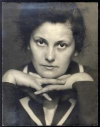 Schwarz-Weiß-Portraitphotographie: Frau in Kostüm stützt Kinn auf verschränkte Hände