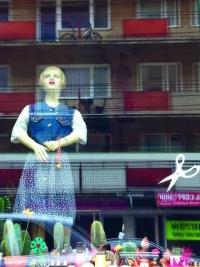 Farbphotographie: Auslage mit Schaufensterpuppe und diversen kleinen Gegenständen, darin spiegelt sich ein Wohnblock mit roten Balkonen
