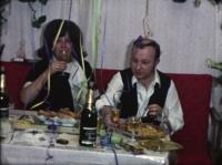 Filmstill: Mann und Frau sitzen auf rotem Sofa, rundherum Girlanden, Frau führt ein Glas Krimsekt zum Mund, Mann raucht und greift zum Glas. Am Tisch Teller mit Snacks.