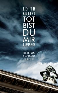 Buchcover: Farbphotographie, Blick nach oben, Fassadendetail und dunkle Wolken, darauf weiße Schrift