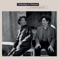 Plattencover mit einer Fotografie mit zwei sitzenden Männern vor einer Holzhütte