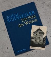 """Ein schlichtes blaues Buch, auf dem mit hellblauen Lettern """"Arthur Schnitzler"""" und in gelben Lettern """"Die Frau des Weisen"""" steht; über dem Buch liegt eine schwarz-weiß Fotografie der sogenannten Schnitzlervilla"""