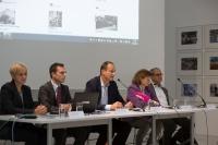 Zwei Frauen und drei Männer auf einem Podium, dahinter wird auf einer Leinwand das Wien Geschichte Wiki gezeigt.
